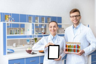 Young smiling chemists in lab coats holding digital tablet and test tubes stock vector