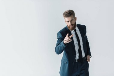 Handsome bearded businessman in stylish suit pointing at camera with finger isolated on grey stock vector