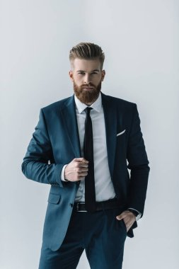 Confident bearded businessman in stylish suit looking at camera  isolated on grey stock vector