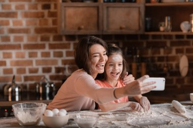 Mother and daughter in flour