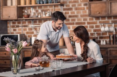 family with cake in kitchen