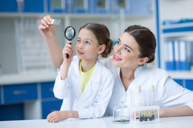 Woman teacher and girl student scientists looking at glass microscope slide through magnifier stock vector