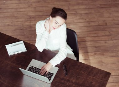 Tired businesswoman using laptop