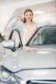 žena drží klíč od auta