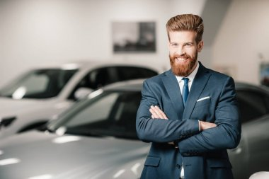 Salesman in suit with crossed arms posing and looking at camera in dealership salon stock vector