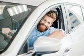 Muž sedící v novém autě