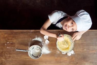 Boy making dough for cookies