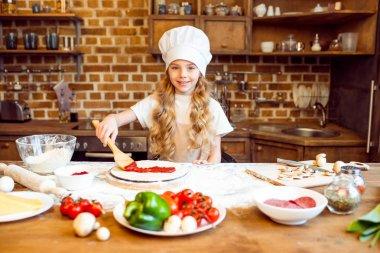 girl putting sauce on dough