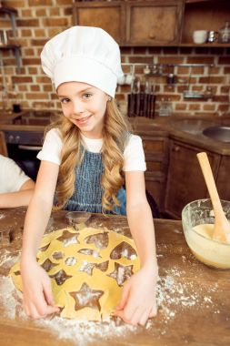 girl making shaped cookies