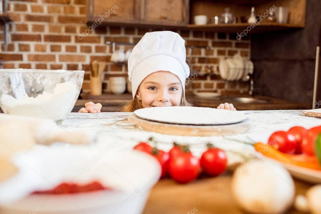 little girl making pizza dough
