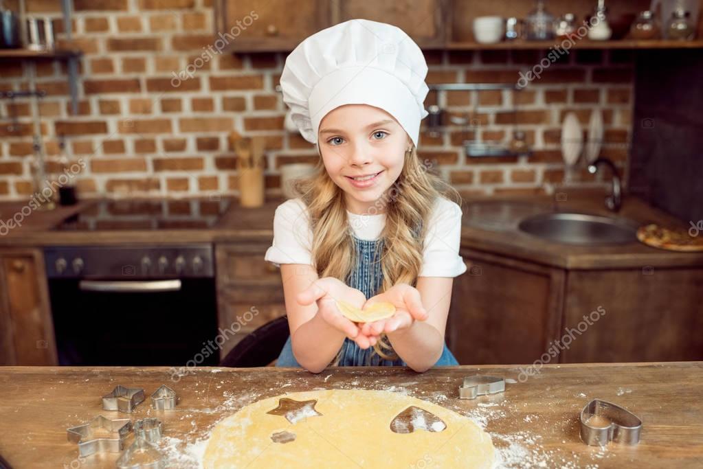 girl holding raw dough