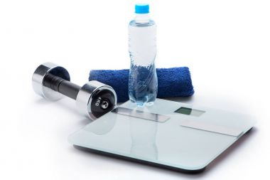 Metallic dumbbell, scales, towel and bottle with water isolated on white. equipment sport and healthy living concept stock vector