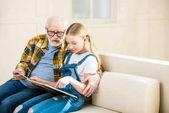 Großvater mit Mädchen liest Buch