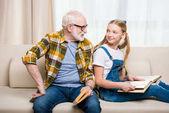 Fotografie Großvater mit Mädchen beim Bücherlesen