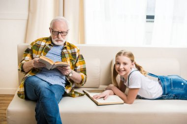 Adorable little girl with grandfather in eyeglasses reading books on sofa stock vector