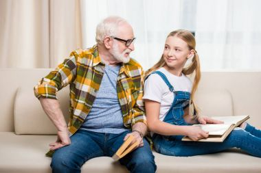 Grandfather with girl reading books