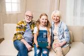 Großeltern und Kind mit digitalem Tablet