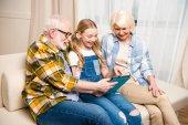 Fotografie Großeltern und Kind mit digitalem Tablet