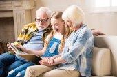 Großeltern und Kind mit Fotoalbum