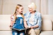 Fotografie Großmutter und Mädchen mit Fotoalbum