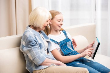 Grandmother and girl with digital tablet