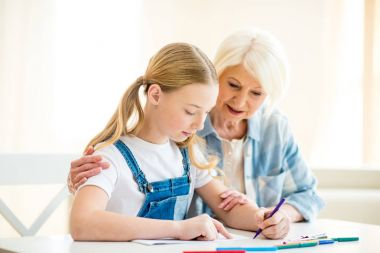 Girl with grandmother drawing