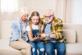 Mädchen mit Großeltern mit Smartphone