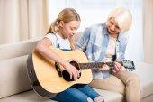 Photo Grandma and girl playing guitar