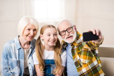 Girl with grandparents taking selfie