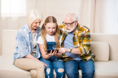 Girl with grandparents using smartphone