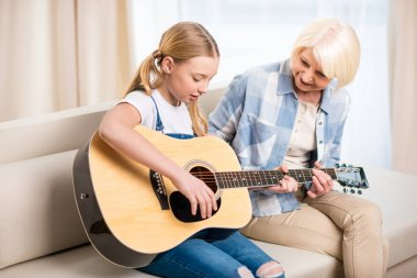 Grandma and girl playing guitar