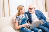 Mädchen mit Großvater mit Laptop