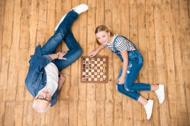 Grandfather and granddaughter playing chess