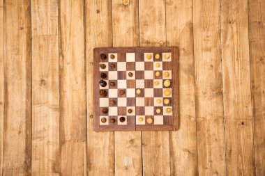 Top view of wooden chessboard with pieces on brown wooden planks stock vector