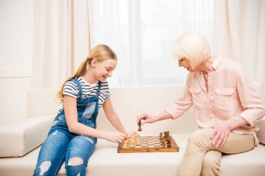 Grandmother and granddaughter playing chess