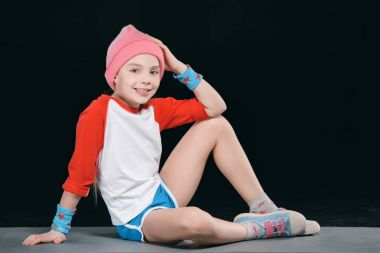 girl in sportswear sitting on mat