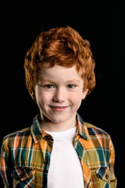 Portrait of adorable redhead boy smiling and looking at camera isolated on black stock vector