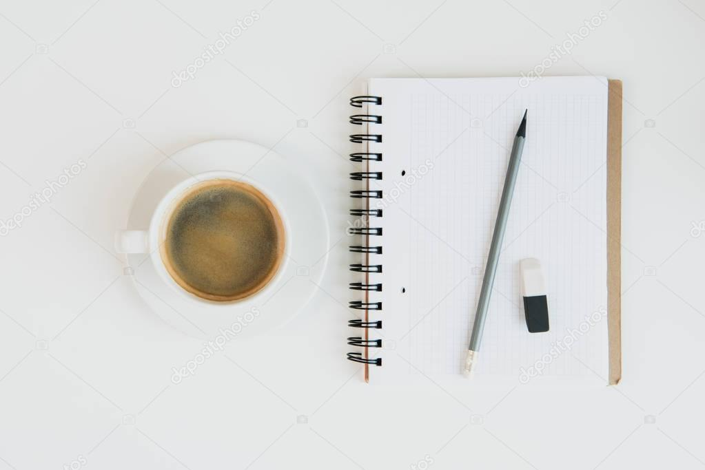 notebook with pencil and cup of coffee