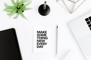 Flat lay with Make something new everyday motivational quote on modern workplace with wireless devices stock vector
