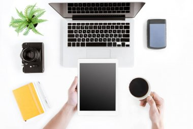 hands holding tablet and coffee cup