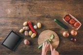Fotografia Mani taglia pezzi di cetriolo sulla scheda di taglio
