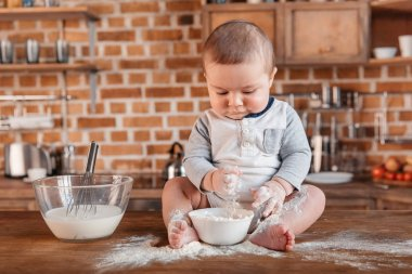 Little boy playing with flour