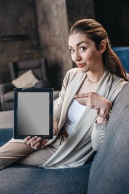 Portrait of young woman pointing on blank screen of digital tablet and looking at camera stock vector