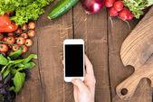 Fotografia Smartphone sulla tabella con le verdure