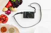Fotografie photo camera with vegetables and spices