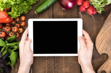 digital tablet over table with vegetables