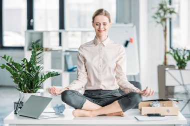 businesswoman meditating in lotus position