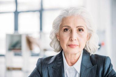 Close-up portrait of beautiful senior businesswoman looking at camera stock vector