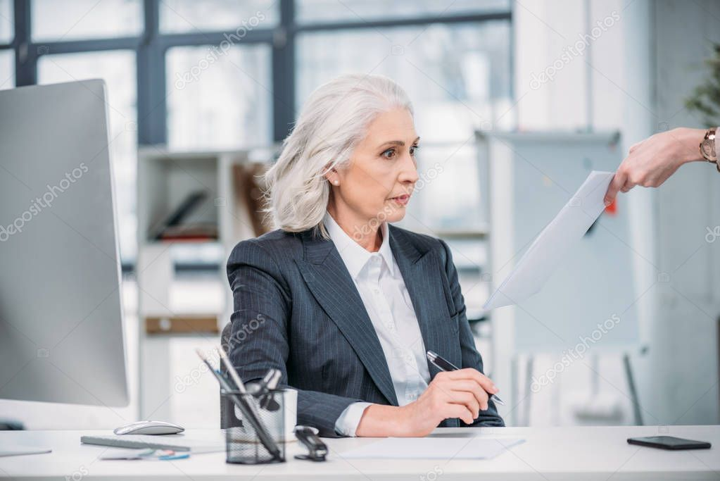 shocked businesswoman looking at documents