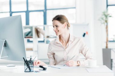 smiling businesswoman working on computer at office